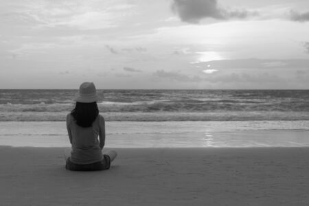 Lonely Asian woman thinking about problems and suffering at the beach during travel holidays vacation outdoors at ocean or nature sea at sunset time, Phuket, Thailand Banco de Imagens - 124874985