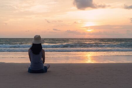 Lonely Asian woman thinking about problems and suffering at the beach during travel holidays vacation outdoors at ocean or nature sea at sunset time, Phuket, Thailand Banco de Imagens - 124874988