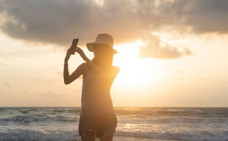 Happy Asian woman taking a selfie to post on social media at beach during travel holidays vacation outdoors at ocean or nature sea at sunset time, Phuket, Thailand