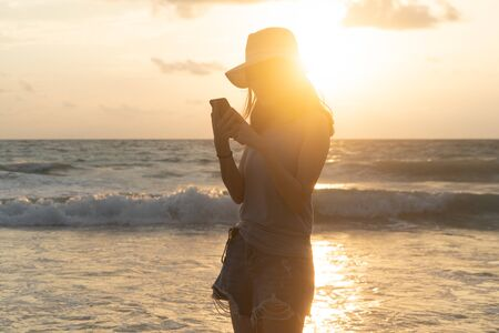 Happy Asian woman using mobile phone or texting messages on social media at beach during travel holidays vacation outdoors at ocean or nature sea at sunset time, Phuket, Thailand Stock Photo