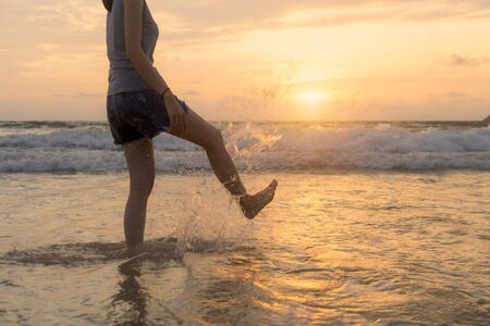 Woman kicking water at the beach during travel holidays vacation outdoors at ocean or nature sea at sunset time, Phuket, Thailand Stock Photo