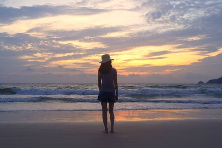 Lonely Asian woman thinking about problems and suffering at the beach during travel holidays vacation outdoors at ocean or nature sea at sunset time, Phuket, Thailand Banco de Imagens - 124867653
