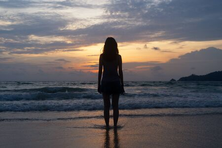 Lonely Asian woman thinking about problems and suffering at the beach during travel holidays vacation outdoors at ocean or nature sea at sunset time, Phuket, Thailand Banco de Imagens - 124867662