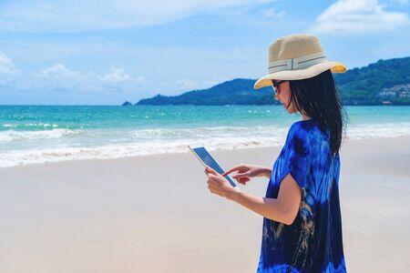 Happy Asian woman using a tablet at the beach during travel holidays vacation outdoors at ocean or nature sea at noon, Phuket, Thailand