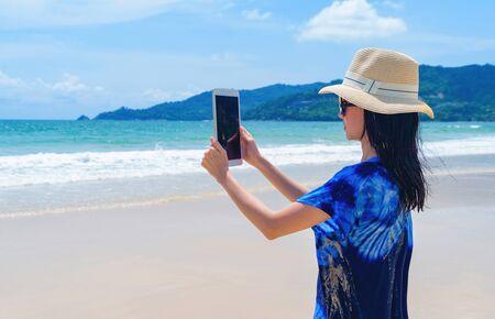Happy Asian woman using mobile phone to take a photo by camera on social media at beach during travel holidays vacation outdoors at ocean or nature sea at noon, Phuket, Thailand