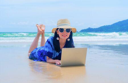 Happy Asian woman using a computer laptop at the beach during travel holidays vacation outdoors at ocean or nature sea at noon, Phuket, Thailand Фото со стока
