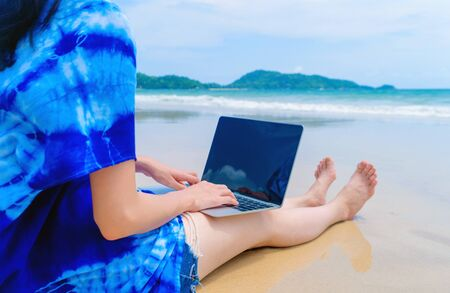 Happy Asian woman using a computer laptop at the beach during travel holidays vacation outdoors at ocean or nature sea at noon, Phuket, Thailand Фото со стока - 124875040