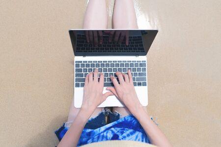 Happy Asian woman using a computer laptop at the beach during travel holidays vacation outdoors at ocean or nature sea at noon, Phuket, Thailand Фото со стока - 124875041