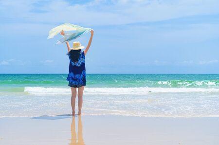 Happy Asian woman relaxing and enjoying at the beach during travel holidays vacation outdoors at ocean or nature sea at noon, Phuket, Thailand Фото со стока - 124875039