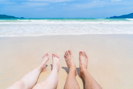 Couple legs sunbathing near the beach during travel holidays vacation outdoors at ocean or nature sea at noon, Phuket, Thailand Фото со стока