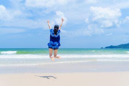 Happy Asian woman jumping, relaxing and enjoying at the beach during travel holidays vacation outdoors at ocean or nature sea at noon, Phuket, Thailand Banco de Imagens
