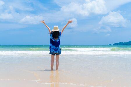 Happy Asian woman relaxing and enjoying at the beach during travel holidays vacation outdoors at ocean or nature sea at noon, Phuket, Thailand Banco de Imagens