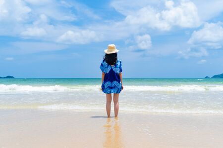 Happy Asian woman relaxing and enjoying at the beach during travel holidays vacation outdoors at ocean or nature sea at noon, Phuket, Thailand Фото со стока - 124875108