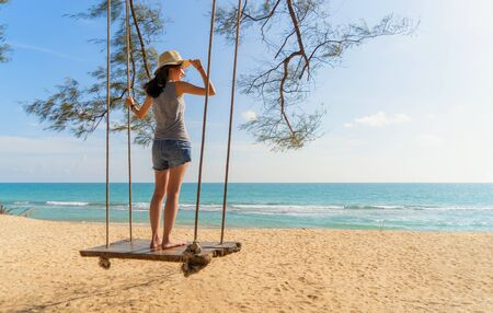 Happy Asian woman swinging on a swing at the beach during travel trip on holidays vacation outdoors at ocean or nature sea at noon, Phuket, Thailand Фото со стока - 124875101