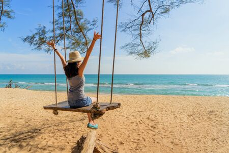 Happy Asian woman swinging on a swing at the beach during travel trip on holidays vacation outdoors at ocean or nature sea at noon, Phuket, Thailand