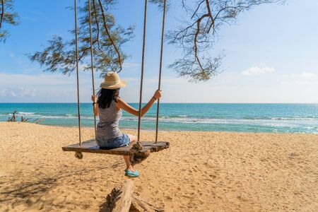 Happy Asian woman swinging on a swing at the beach during travel trip on holidays vacation outdoors at ocean or nature sea at noon, Phuket, Thailand Фото со стока - 124875105