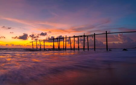 The old wooden bridge and sea wave on the beach at sunset sky background at Khao Pilai, Phangnga, Thailand. Nature landscape