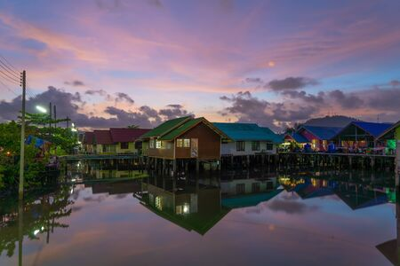 Reflection of Thai traditional Asian fishing village. Floating houses at sunset background in rural area, Phuket City. Thailand. Фото со стока - 124875110
