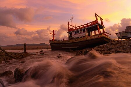 An old shipwreck or abandoned fishing ship with waterfall at sunset sky background in coast of Phuket City, Thailand. Seascape Фото со стока - 124875109