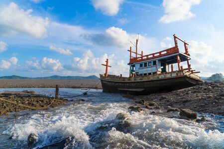An old shipwreck or abandoned fishing ship with waterfall and blue sky background in coast of Phuket City, Thailand. Seascape Фото со стока - 124875112