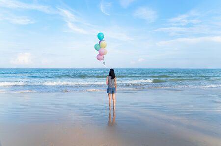 Happy Asian woman holding colorful balloons at the beach during travel trip on holidays vacation outdoors at ocean or nature sea at noon, Phuket, Thailand Фото со стока - 124875111