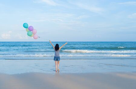 Happy Asian woman holding colorful balloons at the beach during travel trip on holidays vacation outdoors at ocean or nature sea at noon, Phuket, Thailand