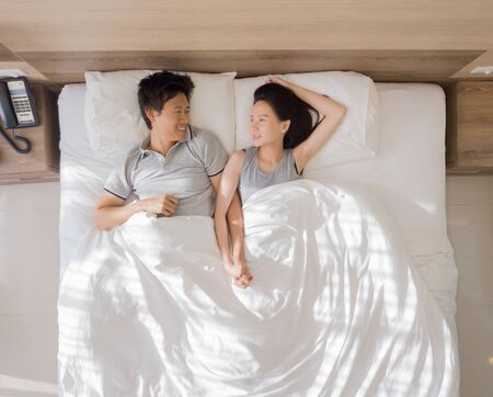 Top view of happy Asian couple smiling, and sleeping together on bed in love and sex concept in a modern bedroom with white blanket in the morning.