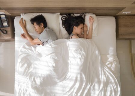 Top view of sad Asian couple sleeping together, thinking about relationship problems, and suffering from depression on bed with white blanket, Фото со стока