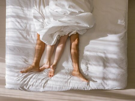 Top view of romantic couple sleeping. bare feet of their legs lying in a bed with white blanket in love and sex concept in modern bedroom. Stock Photo