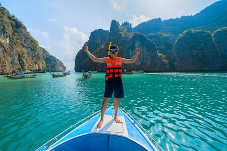 An Asian man, a tourist, standing on a boat to snorkeling in Krabi with turquoise blue sea, Andaman Sea in Thailand.