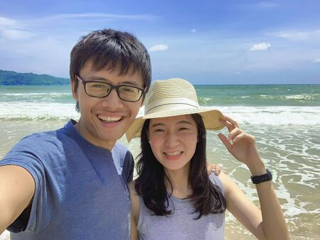 Couple taking selfie at the beach during travel trip on holidays vacation outdoors at ocean or nature sea at noon, Phuket, Thailand Stock Photo