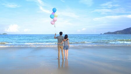 Happy Asian couple holding colorful balloons at the beach during travel trip on holidays vacation outdoors at ocean or nature sea at noon, Phuket, Thailand