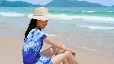 Happy Asian woman wear sunscreen to protect her skin at the beach during travel holidays vacation outdoors at ocean or nature sea at noon, Phuket, Thailand