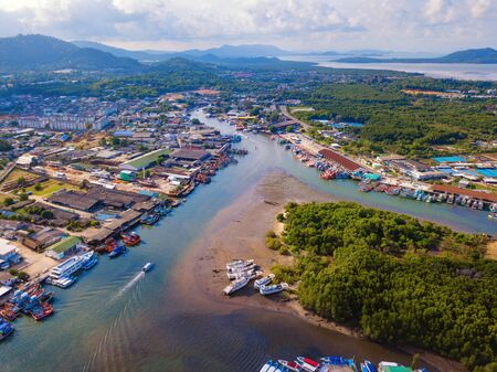 Aerial view of Thai traditional Asian fishing village with boats on sea beach. Residential houses at noon background in rural area, Phuket island. Thailand. Top view Imagens - 124868320