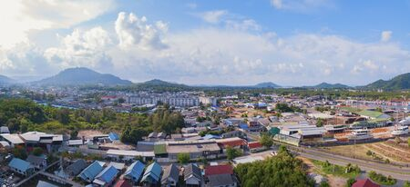 Aerial view of Thai traditional Asian fishing village with boats on sea beach. Residential houses at noon background in rural area, Phuket island. Thailand. Top view Imagens - 124868319