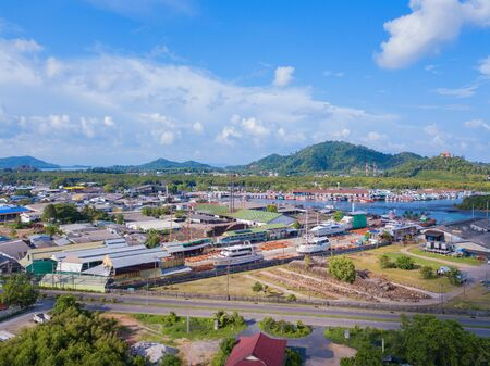Aerial view of Thai traditional Asian fishing village with boats on sea beach. Residential houses at noon background in rural area, Phuket island. Thailand. Top view Imagens - 124868323