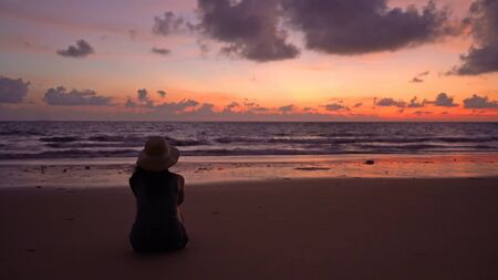 Lonely Asian woman thinking about problems and suffering at the beach during travel holidays vacation outdoors at ocean or nature sea at sunset time, Phuket, Thailand