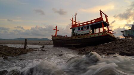 An old shipwreck or abandoned fishing ship with waterfall at sunset sky background in coast of Phuket City, Thailand. Seascape Stock Photo - 124868333