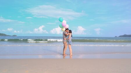 Happy Asian couple kissing, holding colorful balloons at the beach during travel trip on holidays vacation outdoors at ocean or nature sea at noon, Phuket, Thailand Stock Photo