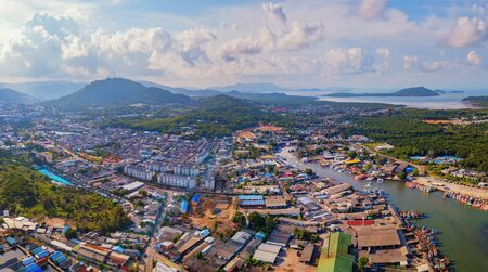 Aerial view of Thai traditional Asian fishing village with boats on sea beach. Residential houses at noon background in rural area, Phuket island. Thailand. Top view Imagens - 124874861