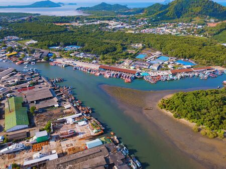 Aerial view of Thai traditional Asian fishing village with boats on sea beach. Residential houses at noon background in rural area, Phuket island. Thailand. Top view Imagens - 124874862