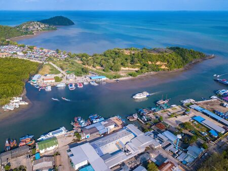 Aerial view of Thai traditional Asian fishing village with boats on sea beach. Residential houses at noon background in rural area, Phuket island. Thailand. Top view Imagens - 124874863