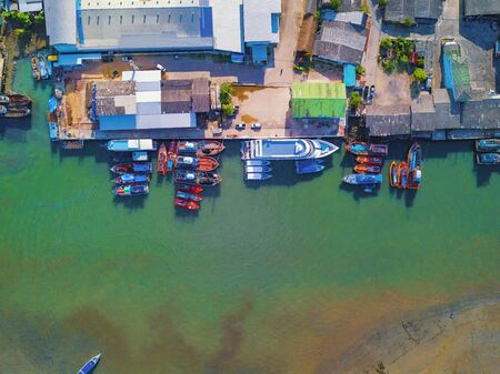 Aerial view of Thai traditional Asian fishing village with boats on sea beach. Residential houses at noon background in rural area, Phuket island. Thailand. Top view Imagens - 124874865