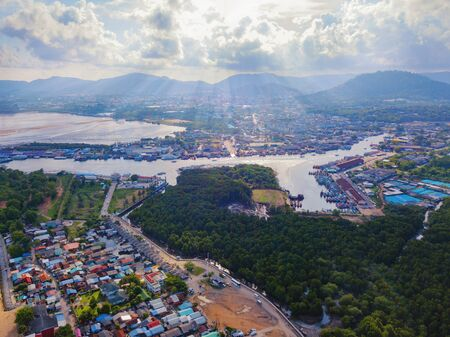 Aerial view of Thai traditional Asian fishing village with boats on sea beach. Residential houses at noon background in rural area, Phuket island. Thailand. Top view