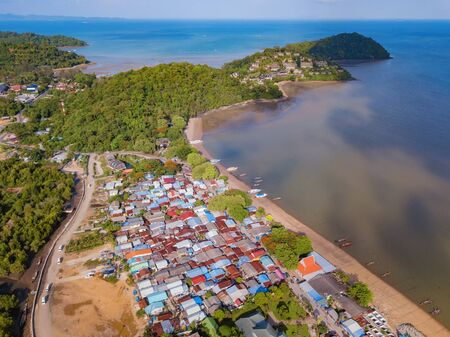 Aerial view of Thai traditional Asian fishing village with boats on sea beach. Residential houses at noon background in rural area, Phuket island. Thailand. Top view Imagens - 124874866