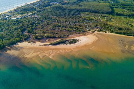 Aerial view of natural forest trees with sand, tropical beach and waves rolling into the shore, Andaman sea, Phuket bay island in summer season, Thailand. Top view Фото со стока - 124874871