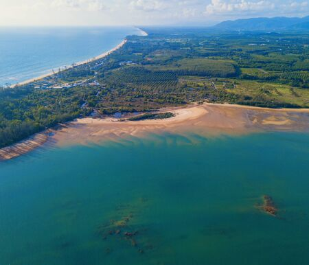 Aerial view of natural forest trees with sand, tropical beach and waves rolling into the shore, Andaman sea, Phuket bay island in summer season, Thailand. Top view