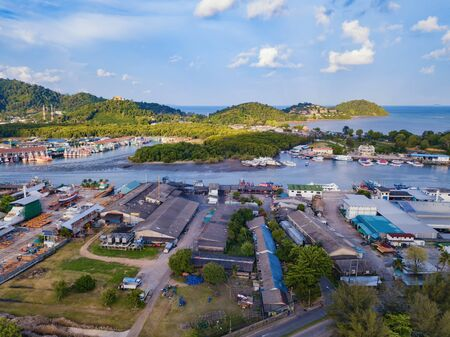 Aerial view of Thai traditional Asian fishing village with boats on sea beach. Residential houses at noon background in rural area, Phuket island. Thailand. Top view Imagens - 124868549