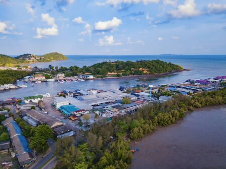 Aerial view of Thai traditional Asian fishing village with boats on sea beach. Residential houses at noon background in rural area, Phuket island. Thailand. Top view Imagens - 124868554