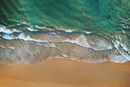 Aerial view of beach with waves rolling into the shore with copy space for travel, holidays vacation outdoor background, Andaman sea, Phuket bay island in summer season, Thailand. Top view Stock Photo